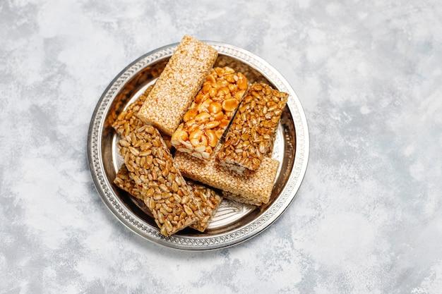 Гранола бар. здоровая сладкая десертная закуска. кунжут, арахис, подсолнечник в мёде. козинак - грузинская национальная еда, восточная сладость. вид сверху на бетон