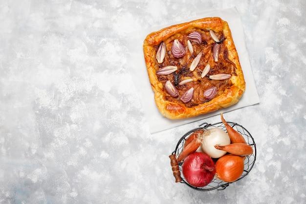 パイ生地と様々な玉ねぎエシャロット、赤、白、黄色の玉ねぎ、トップビューでフランス風玉ねぎパイガレット
