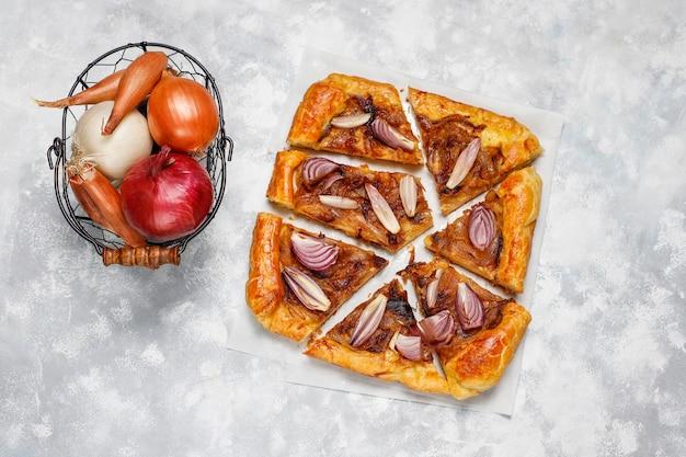 Французский галет с луковым пирогом с слоеным тестом и различным луком шалот, красный, белый, желтый лук, вид сверху