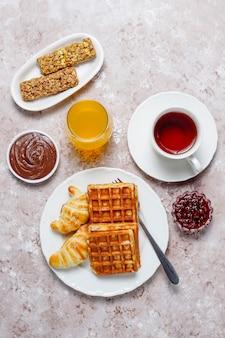 コーヒー、オレンジジュース、ワッフル、クロワッサン、ジャム、ナッツペーストの光、トップビューで美味しい朝食
