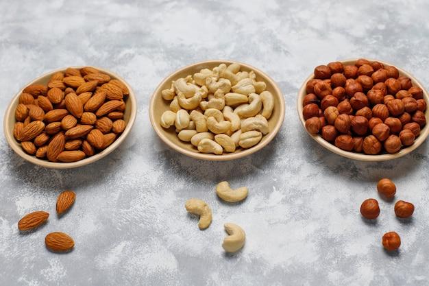 Ассортимент орехов в керамических пластинах. кешью, фундук, грецкие орехи, фисташки, орехи пекан, кедровые орехи, арахис, изюм. вид сверху