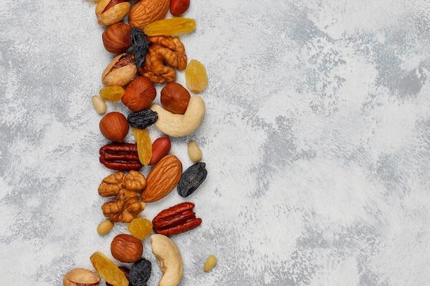 セラミックプレートのナットの品揃え。カシューナッツ、ヘーゼルナッツ、クルミ、ピスタチオ、ピーカンナッツ、松の実、ピーナッツ、レーズン。トップビュー