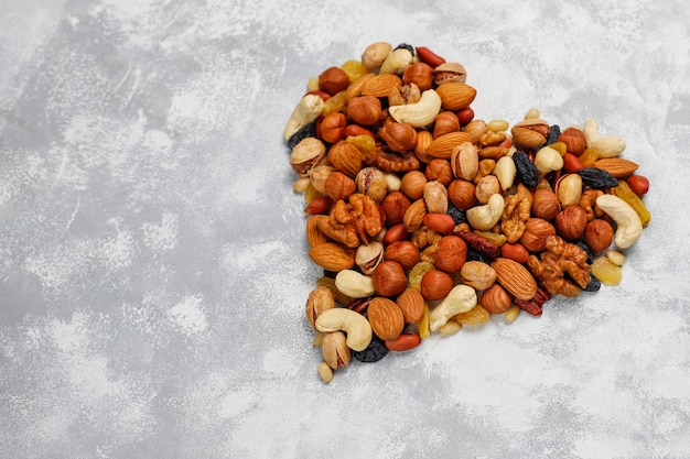 ハートの形のナッツの品揃えカシューナッツ、ヘーゼルナッツ、クルミ、ピスタチオ、ピーカンナッツ、松の実、ピーナッツ、レーズン。トップビュー