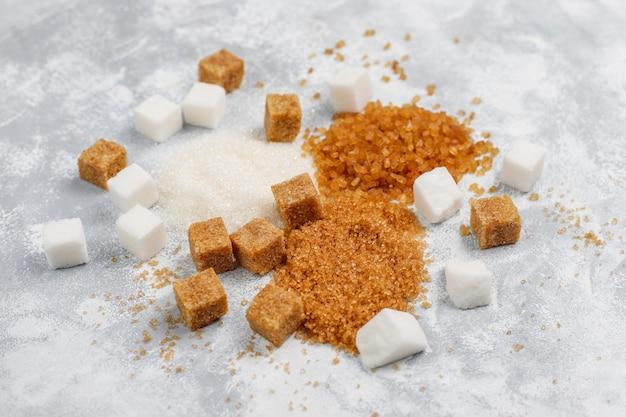 さまざまな種類の砂糖、ブラウンシュガー、白のコンクリート、トップビュー