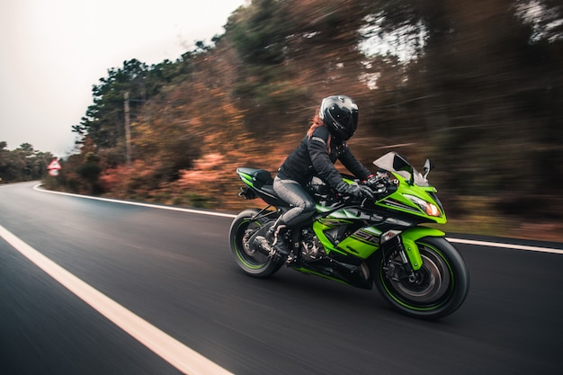 Женщина водитель за рулем зеленого неонового цвета мотоцикла на дороге.