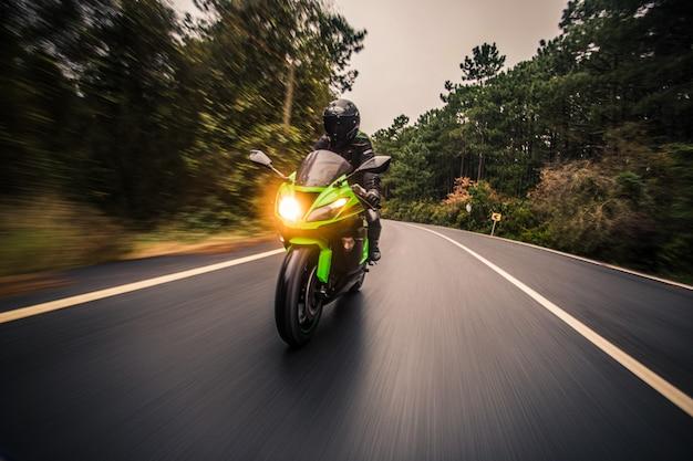 За рулем зеленого неонового цвета мотоцикл по бездорожью в сумерках времени.