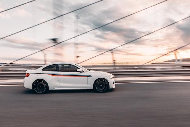 Белый спортивный седан с красочным тюнингом едет по мосту.