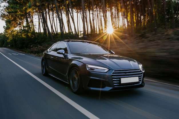 日没の黒いスポーツ車の高速道路ドライブ。