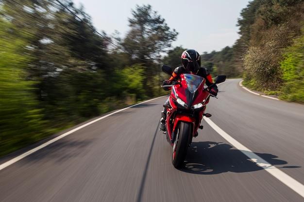 Красный мотоцикл вождения на дороге.
