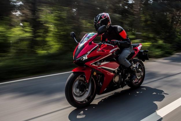 Красный мотор на велосипеде по дороге.