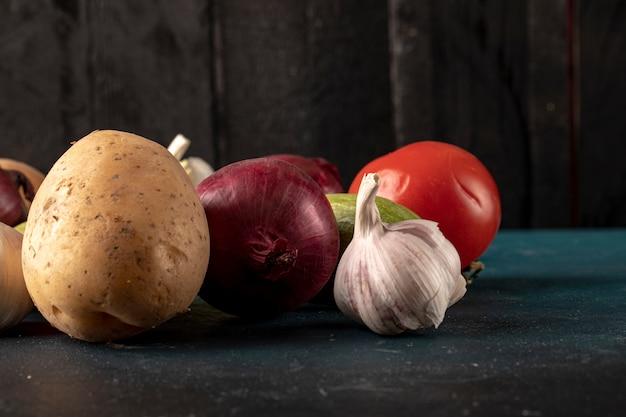 Овощное ассорти, включая чесночные перчатки, картофель, лук и помидоры.