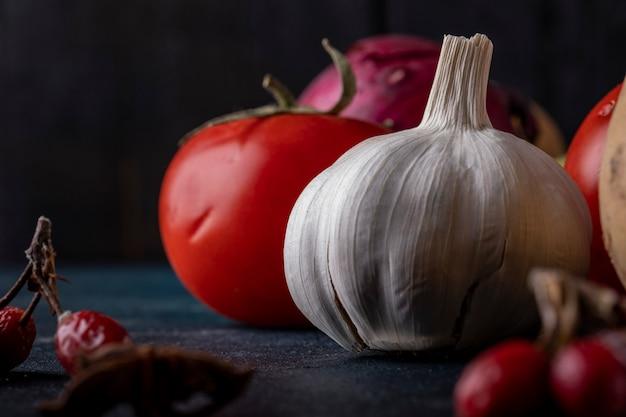 Перчатки и томаты чеснока на черной таблице.