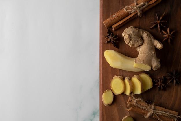 Нарезанные и очищенные растения имбиря на деревянной доске с палочками аниса и корицы