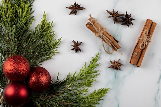 コーナーの緑の枝とシナモン、中央のアニスに赤いクリスマスツリーのボール。