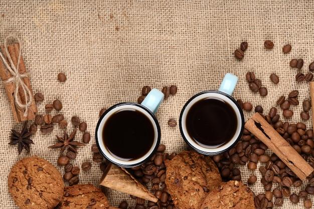 Кофейные чашки и бобы обрамление с печеньем.