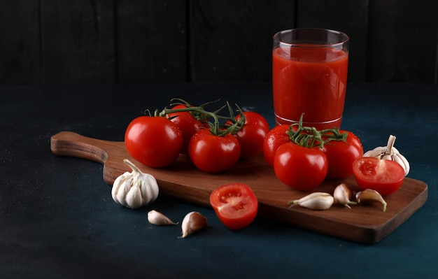 Красные томаты и перчатки чеснока на деревянной доске с стеклом сока на голубой предпосылке.