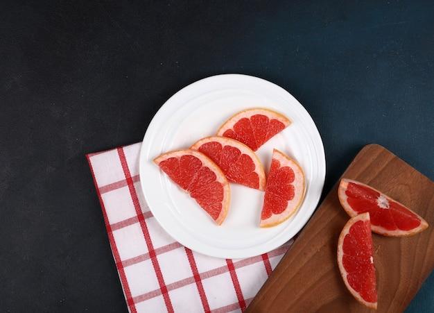 Нарезанный грейпфрут на синем фоне.