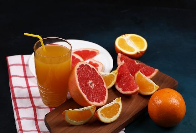 Стакан сока с апельсином и грейпфрутами.