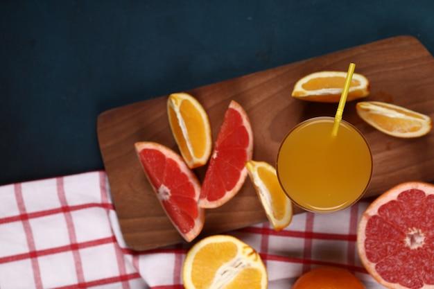 Ломтики апельсина и грейпфрута с бокалом напитка на деревянной доске. вид сверху.