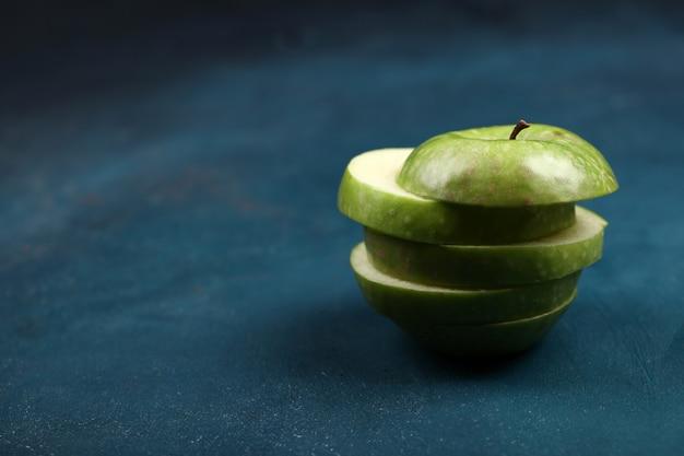 Круглое нарезанное зеленое яблоко.