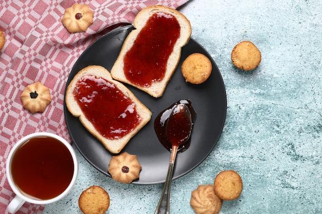 Два ломтика тоста с красным вареньем в черной тарелке с печеньем вокруг