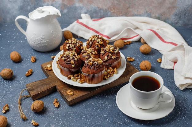 Шоколадно-ореховые маффины с кофейной чашкой с грецкими орехами на темной поверхности