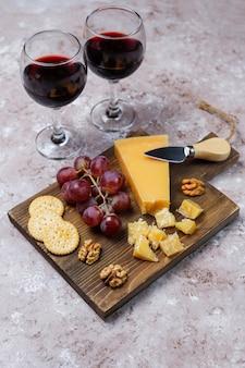 ハードチーズ、チーズナイフ、赤ワイングラス、茶色のコンクリート表面のブドウとチーズボード