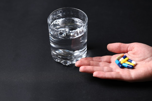 人と水のガラスの手でカラフルな医療薬