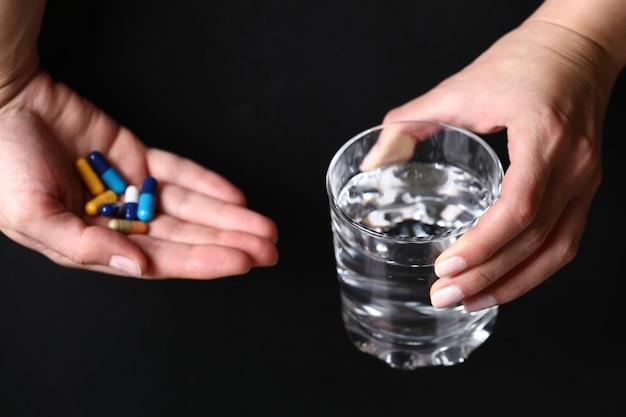コップ一杯の水と医療薬を手に持って。