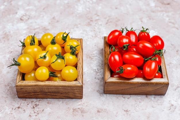 Расположение красочных свежих томатов ассорти на бетонной поверхности