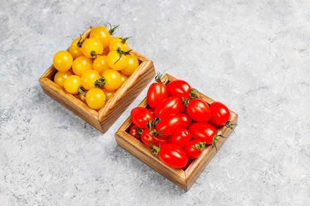 コンクリート表面上のカラフルな新鮮なトマトの盛り合わせ