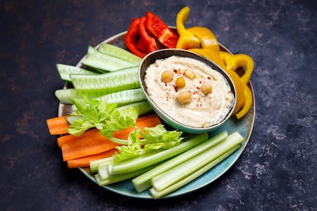 暗い茶色またはコンクリートの表面にフムスと新鮮な有機野菜サラダのプレート