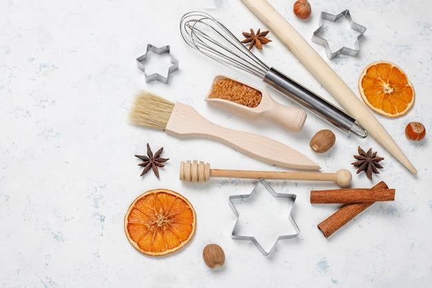 Кухонная посуда со специями для печенья и формочки на светлой поверхности