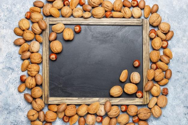 コンクリート表面上のナッツの品揃え。ヘーゼルナッツ、クルミ、ピーカンナッツ、ピーナッツ、アーモンド、トップビュー