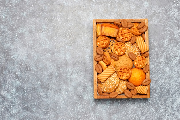 灰色の表面に木製のトレイにさまざまなクッキー