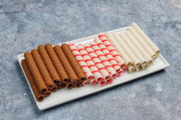 Тарелка с вкусными вафельными трубочками на бетонной поверхности