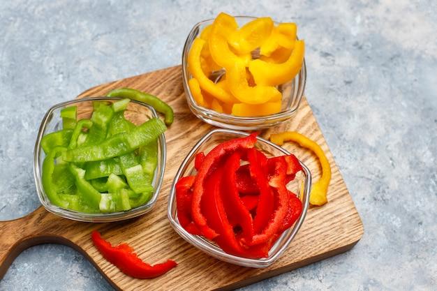 明るい面にカラフルなピーマンのスライスとまな板。異なる色のピーマンのスライス、野菜サラダ成分、健康食品の調理、トップビュー