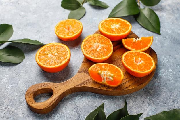 Свежие нарезанные апельсины на разделочную доску на бетонной поверхности