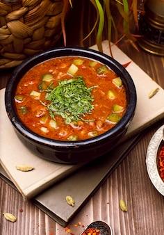 本の上に黒のボウルにハーブとトマトのズッキーニ野菜スープ