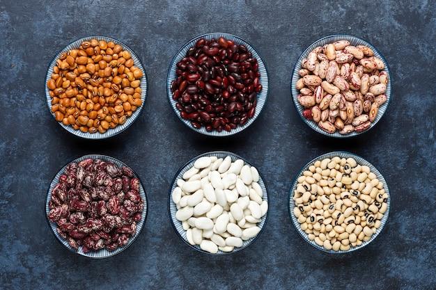 Бобовые и фасоль ассорти в разных чашах на светлой каменной поверхности. вид сверху. здоровая веганская протеиновая пища.