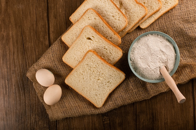 Ломтики хлеба с миской муки и яиц