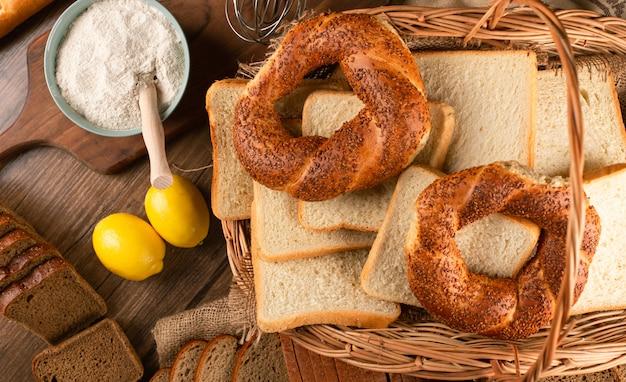 Бублики и ломтики белого хлеба в корзине с мукой и лимонами