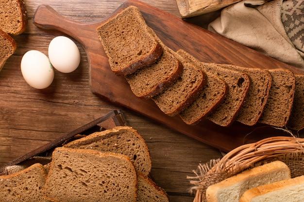 卵とキッチンボード上の茶色のパンのスライス
