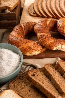 Вкусные бублики с ломтиками хлеба и миской муки