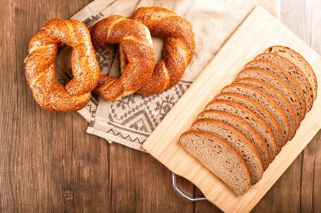 Бублики и ломтики хлеба в корзине и на скатерти