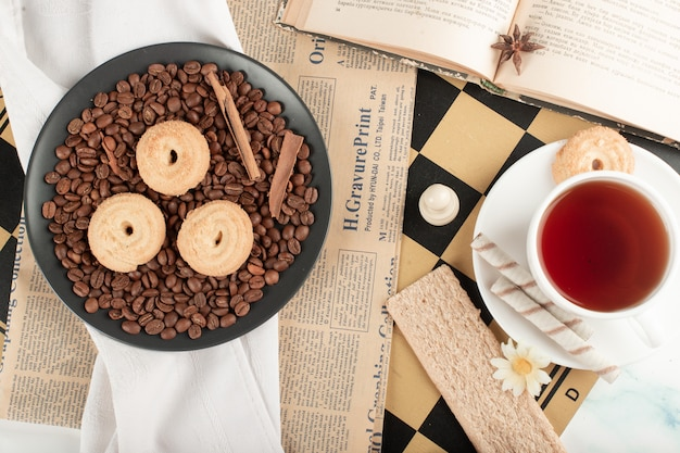 Чашка чая и кофе в зернах с печеньем