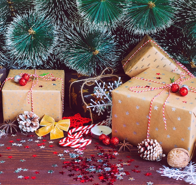 松ぼっくりモミの枝で飾られたお祝いテーブルの上のクリスマスホリデーギフトボックス