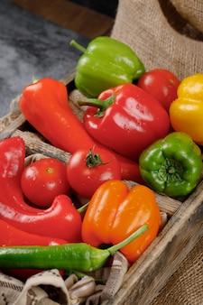 素朴なトレイに赤、緑、黄色の野菜。上面図。