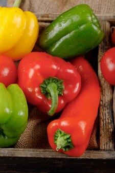 Красные и зеленые болгарские перцы в деревенском подносе. вид сверху.
