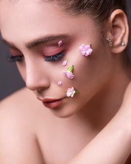 彼女の顔に花を持つ女性モデル
